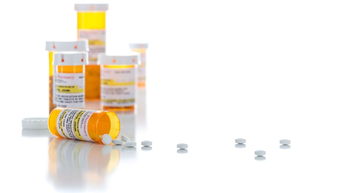 Non-Proprietary Medicine Prescription Bottles and Spilled Pills Isolated on a White Background.