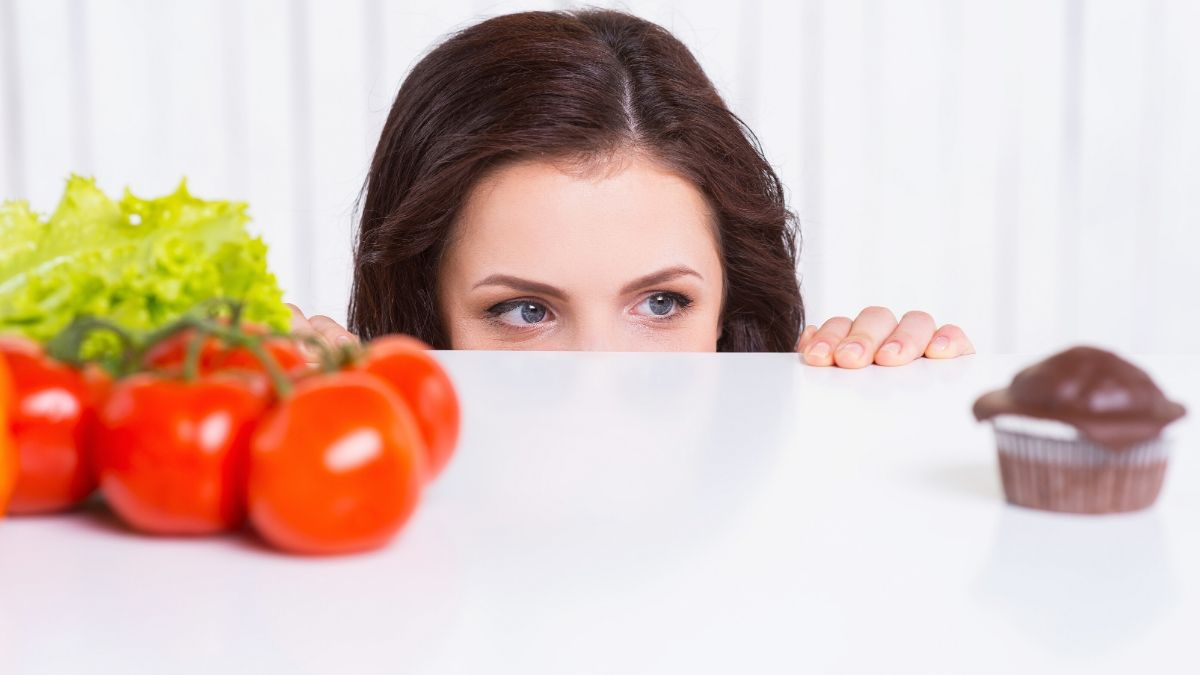 Thoughtful young woman looking out of the table while fresh vegetables and chocolate muffin laying on it