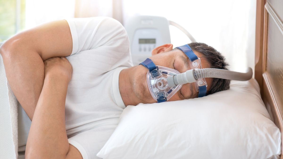 Man sleeping in bed wearing CPAP mask
