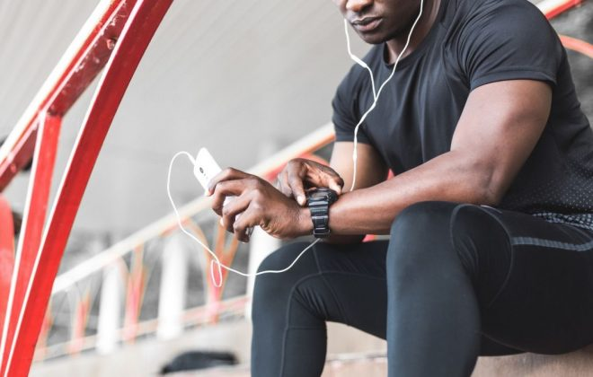 a black man resting after a workout and listening to music and watching a sports watch